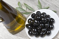 Olive oil and a plate with black olives. Stock Images
