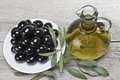 Olive oil and a plate with black olives. Stock Photography