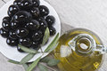 Olive oil and a plate with black olives. Stock Image
