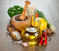 Olive oil spices and vegetables on a brown table Stock Images