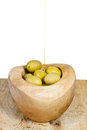 Olive oil in thin trickle flows on olives in bowl wooden close up isolated white background Royalty Free Stock Photography