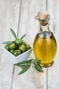 Olive oil on a wooden background glass bottle of and green olives Royalty Free Stock Images