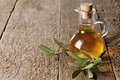 Olive oil on a wooden table with leaves Stock Photo