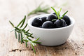 Olives black with rosemary on wood Stock Images