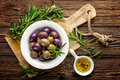 Olives in bowl with olive oil on dark wooden rustic background, above view, italian cuisine Royalty Free Stock Photo