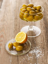Olives and lemons bowl of with lemon salt on wooden table shallow focus vibrant color Stock Photos