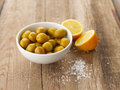 Olives and lemons bowl of with lemon salt on wooden table shallow focus vibrant color Royalty Free Stock Image