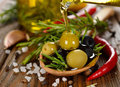 Olives with rosemary and olive oil on a brown table close up Stock Image