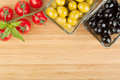 Olives, tomatoes and basil on cutting board Royalty Free Stock Photo