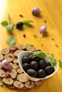 Olives in a white bowl on wooden table Royalty Free Stock Photos