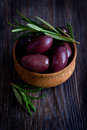 Olives in wooden bowl with rosemary Stock Photo