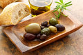 Olives on wooden plate and bread Stock Photos