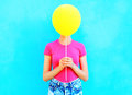 Сolorful woman hiding face yellow air balloon having fun over blue Royalty Free Stock Photo