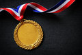 Olympic gold medal on black with blank face for text concept for winning or success Stock Photo