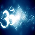 Om aum symbol on a blue background with some glitters and sparkles Royalty Free Stock Photos