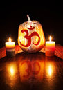 Om halloween pumpkin with carved symbol glowing inside and candles nearby at black background Stock Image