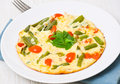 Omelette with green beans and cherry tomatoes on plate Royalty Free Stock Photos
