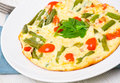 Omelette with green beans and cherry tomatoes on plate Stock Photo