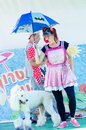 Omer (Beer-Sheva), ISRAEL -Clowns with blue umbrella and a white poodle, July 25, 2015 Royalty Free Stock Photo