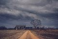 Ominous clouds over an abandoned farm house Royalty Free Stock Photo