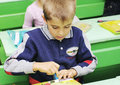 Omsk russia september schoolboy third grader glues applique doing hand creative work at school desk in classroom Royalty Free Stock Photography