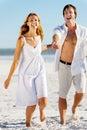 Onbezorgd lopend strandpaar Stock Fotografie