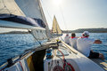 Onboard view of racing sailing yacht with a crew sitting on the starboard side Royalty Free Stock Photo