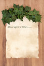 Once upon a time story phrase on old parchment with ivy over oak background Royalty Free Stock Image