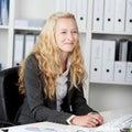 Onderneemster smiling while looking weg bij bureau Stock Afbeeldingen