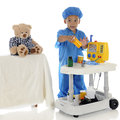 This one an adorable preschool doctor in blue scrubs questioning about the medication he should be giving his patient toy bear Stock Images
