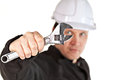 One adult male handyman professional technician repairman wearing black coveralls uniform white hardhat spanner tool isolated Stock Image