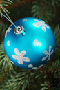 One blue christmas ball handing on a tree green Stock Image