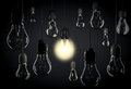 One bulb lighting up room with hanging light bulbs on wires