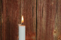 One burning candle at an old red wall Royalty Free Stock Photo