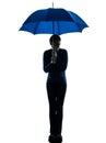 Anxious woman holding umbrella silhouette Royalty Free Stock Photo