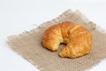 One croissant on spuare frayed burlap Royalty Free Stock Photo