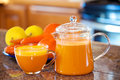 One cup of orange colored juice on kitchen counter with fruit an Royalty Free Stock Photo