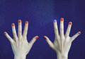 One different nail color in finger in caucasian hands. Red and blue painted fingernails. Royalty Free Stock Photo