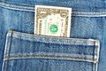 One dollar bill sticking in the back pocket of denim jeans blue Stock Photography