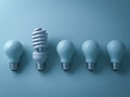 One eco energy saving light bulb different and stand out from old incandescent lightbulbs on cyan Royalty Free Stock Photo