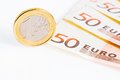 One euro coin on 50-euro banknotes Stock Photo