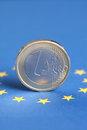 One euro coin on the flag of eu a stands Stock Image