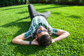 One fashion middle eastern man with beard, fashion hair style is resting on beautiful green grass day time. Royalty Free Stock Photo
