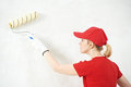 One female house painter worker painting and priming wall with painting roller Royalty Free Stock Photo