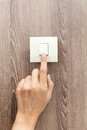 One finger switching turned on off press the button wood wall background Stock Images