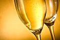 One flute of champagne and one empty with golden bubbles and space for text against background Stock Image