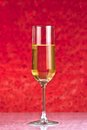 One flute of golden champagne abstract red background on bokeh Royalty Free Stock Photo
