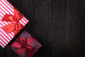 One gift box with an red big ribbon on old wooden dark brown bac Royalty Free Stock Photo