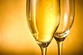 One glass of champagne and one empty with golden bubbles and space for text against background Stock Images