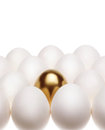 One gold egg lays among common white eggs Royalty Free Stock Photo